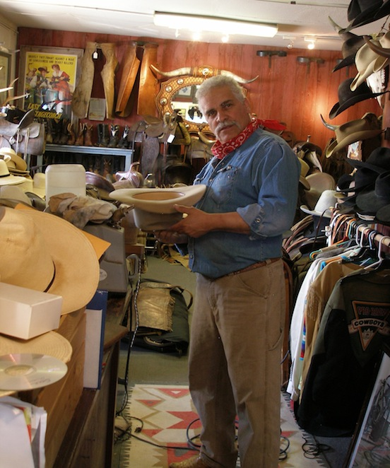 Randy Rodriquez, owner Rio Bravo Trading Company blocking Thom Valenza's hat<br>411 So. Guadalupe Street, Santa Fe, N.M 